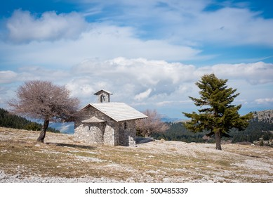 Winter landscape with a small chapel, trees and blue sky with clouds  on mountain Helmos near Kalavryta town in Greece