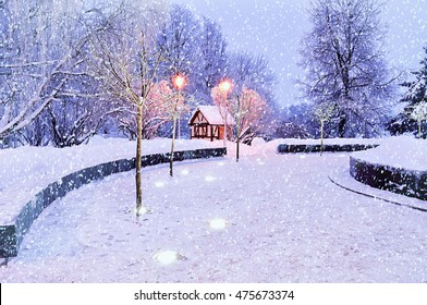 Winter landscape - small house among the illuminated frosty trees under falling snowflakes. Night winter scene with Christmas and New Year festive mood