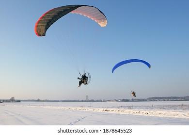 Paysage hivernal avec neige et ciel bleu. Deux ambulanciers survolent les champs