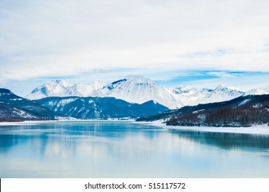 Winter landscape with snow covered mountains beside a frozen lake