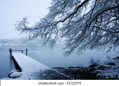 Winter landscape with snow covered tree and pier. Lake covered with thin ice. Switzerland