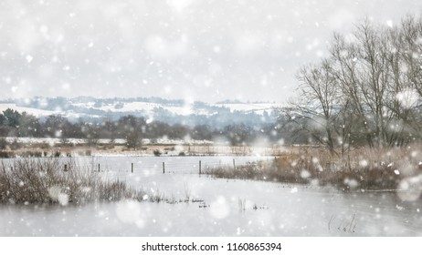 Winter landscape with snow falling and covering ground and foliage in English countryside