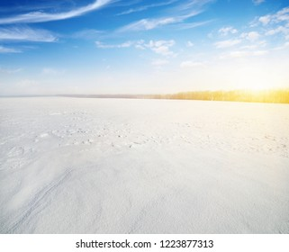 Winter landscape. Snowcovered fields on  sky and sun.