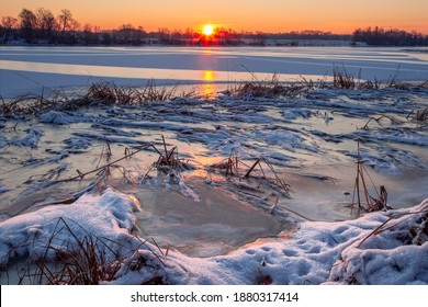 Winter landscape with snow-covered river bank at sunrise. Frozen grass covered with snow in the foreground, a river with glistening ice reflects the sun. A sparse forest in the background. No people