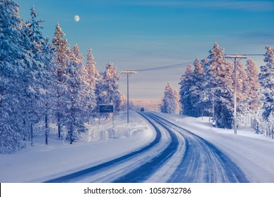 Winter landscape with snow-covered road and pine trees landscape in Northern Finland in January. Trees are covered with hoarfrost and snow.  Moon in the light blue sky. Color toning applied.