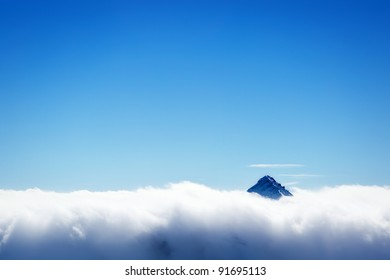 Winter landscape - snowed mountain's top over white clouds cover and clear blue sky background