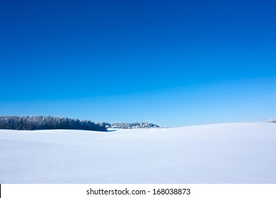 Winter Landscape with Snowy Field and Blue Sky. Copy Space.
