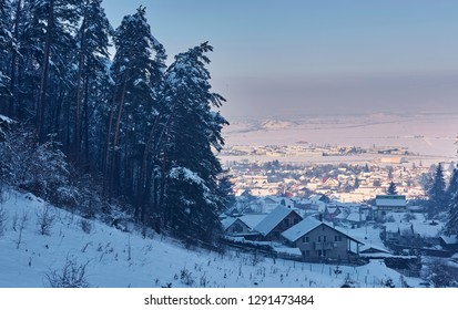 Winter landscape, snowy fir tree forest and idyllic village at the base of Piatra Mare mountain, Brasov county, Romania.