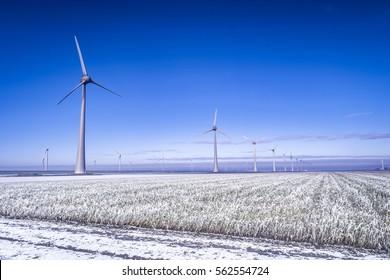 Winter landscape with snowy frosty land and huge windmills by windmill farm Westermeerdijk Urk Flevoland Netherlands January 2017