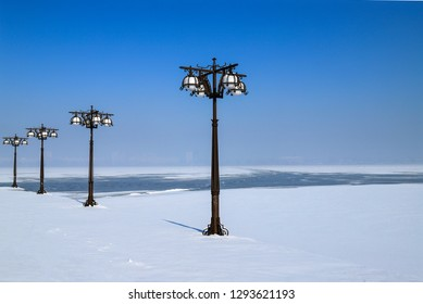 Winter landscape of a snowy river and embankment with vintage metal lanterns, Dnepropetrovsk, Dnipro city , Ukraine,