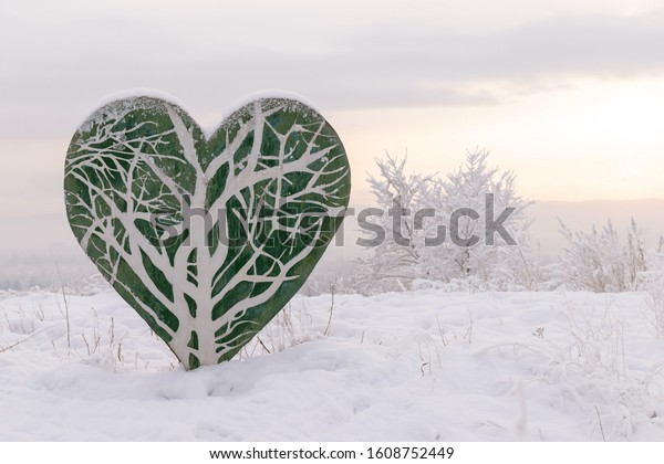 Winter landscape - stylized green heart made of wood against a sunset sky in the snow