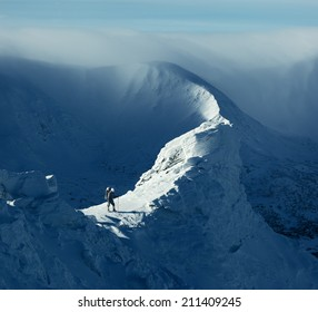 Winter landscape. Sunny day in the mountains. Tourist standing on a rock