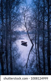 Winter landscape with sunset and boat at evening in Finland