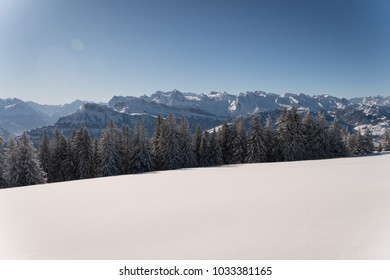 Winter landscape in the Swiss Alps on a sunny day with lots of fresh snow and snow covered mountain peaks and forest