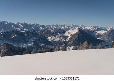 Winter landscape in the Swiss Alps on a sunny day with lots of fresh snow and snow covered mountain peaks and lots of trees