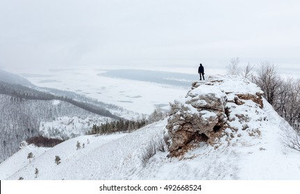 Winter landscape. Tourist standing on the hill in a winter day. Man standing alone on the snowy mountain. view from Strelnaya Mountain at Zhiguli Mountains and the Volga River, Samara, Russia