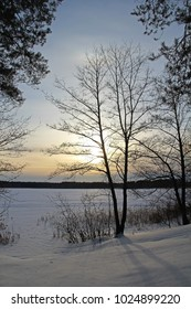 Winter landscape with trees, beautiful frozen lake and bushes at sunset. Russia.