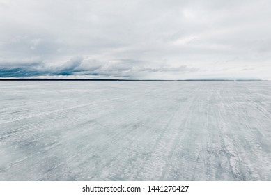 Winter landscape. A view of the frozen snow-covered lake. Forest in the background. Stormy evening clouds. Onega lake, Karelia, Russia