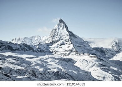 winter landscape with a view of the Matterhorn in calm weather, covered by clouds at the bottom