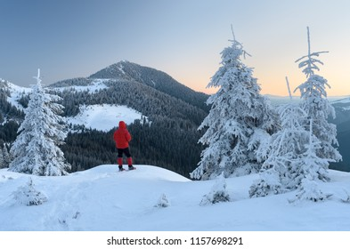 Winter landscape with a view of the mountain peak. Tourist on a hike in snowshoes