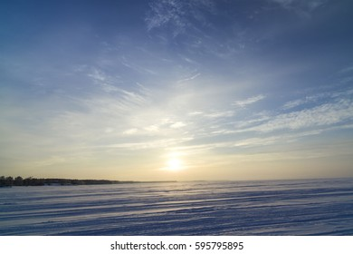 Winter landscape with a view of the setting sun