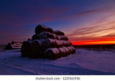 winter landscape with view of snow-covered straw bales in field at sunset