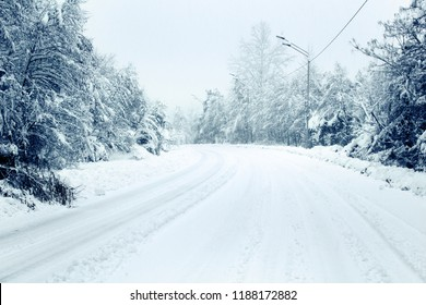 Winter Landscape with walking winter road in deep snow, frost on tree branches, snowy forest, winter maintenance, forest road