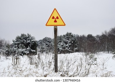 Winter landscape with warning sign of radiation hazard in the area of radioactive fallout