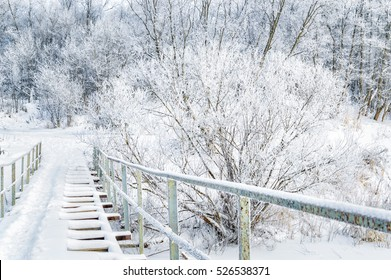 Winter landscape. Wooden bridge over the frozen river. Snow covered trees and bushes. Christmas greetings. New Year.