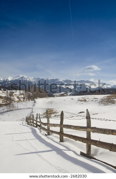 Winter landscape with wooden fence and mountains in the background