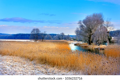 Winter landscape of woods and river covered with ice and snow in Masuria lakes district in Poland - Elk river estuary to Haleckie lake
