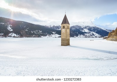 Winter landscapein the Alps with the famous sunken church tower in Reschensee (Resia lake) on the border between the South Tyrol (Italian Alps) and Austria.
