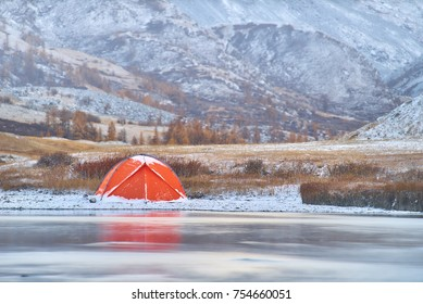 Winter or late fall in mountains, lonely camping and a river or a lake. Red tent is located on the river bank.