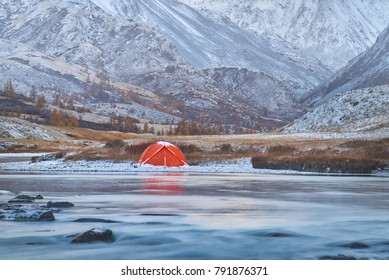 Winter or late fall in mountains. lonely camping and a river or a lake. Red tent is located on the river bank. terrain presents to be rocky highland with narrow