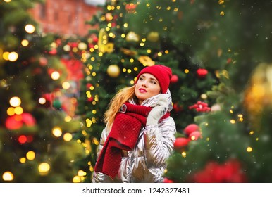 Winter lifestyle fashion portrait of pretty young woman walking on the christmas market. On decorated Christmas trees background. Enjoying holidays. Wearing stylish hat, silver down jacket. Christmas