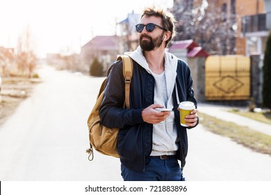 Winter Lifestyle Portrait of handsome man with beard walking in the city, drink coffee and use smartphone.