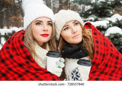Winter lifestyle portrait of two pretty girl friends walking through the snowy spruce forest. Drinking coffee and basking under the plaid. Wearing stylish down jackets and hats. Winter spruce forest.
