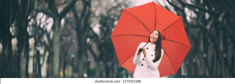 Winter lifestyle young woman walking in nature outdoors with red umbrella - City living people lifestyle banner panorama.