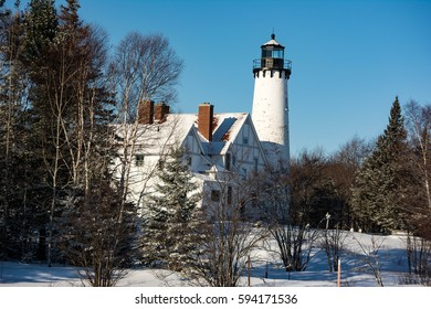 winter lighthouse with pine trees and snow.