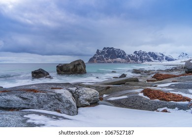 Winter in Lofoten, Uttakleiv, famous beach moody clouds, snow and mountains in background