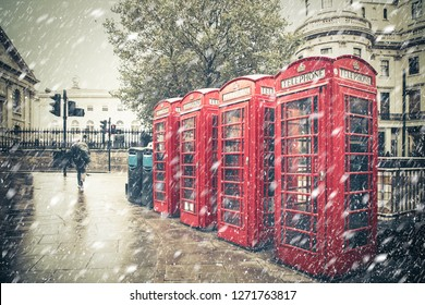 Winter London street scene with iconic red phone booths with snow falling