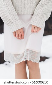 Winter look, girl in warm woolen sweater and a skirt made of natural silk with lace