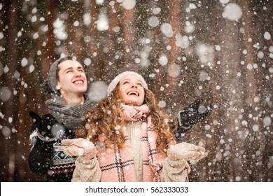 Winter Love Story, a young couple walking and having fun in a winter forest under heavy snow, catching snowflakes in toning