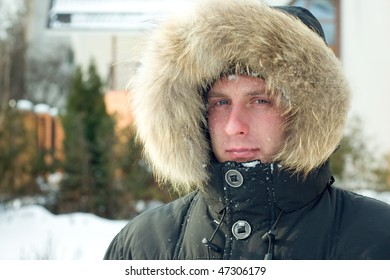 Winter - man in warm jacket with furry hood in the yard