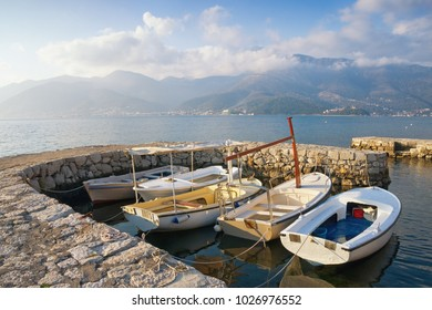 Winter Mediterranean landscape with boats in small harbor. Bay of Kotor, Tivat, Montenegro