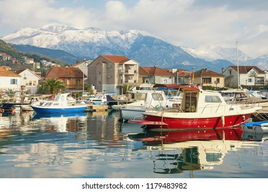 Winter Mediterranean landscape. Fishing boats in harbor on background of snowy mountains. Montenegro, Bay of Kotor. View of Marina Kalimanj in Tivat city and snow-capped of Mount of Lovcen