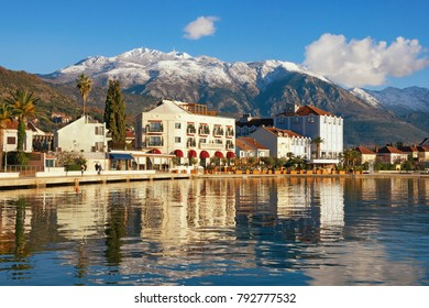 Winter Mediterranean landscape. Montenegro, embankment of Tivat city and snow-capped peaks of Lovcen mountain
