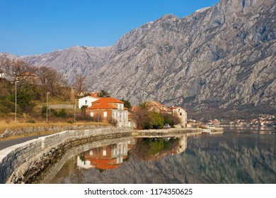 Winter Mediterranean landscape. Small village at foot of mountains; houses with red roofs reflected in water. Montenegro, Bay of Kotor, Adriatic Sea