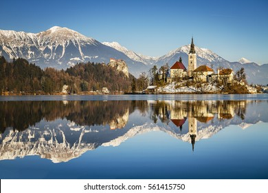 Winter mirror reflection view of Bled castle, Bled church of Saint Martin and Hochstuhl Karawanks. Slovenia, Europe. Snow covered mountains in the background. Clear sky. Slovenia's tourism landmark.