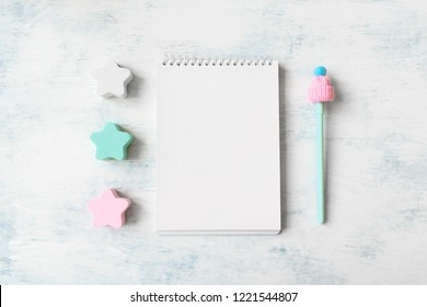 Winter mockup with open white three pastel blue and pink star, notebook and pen. Minimal winter pastel colored background with copy space. Flat lay, top view
